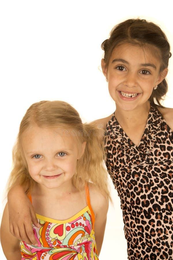2 молодых счастливых девушки нося купальники стоя и усмехаясь стоковое фото