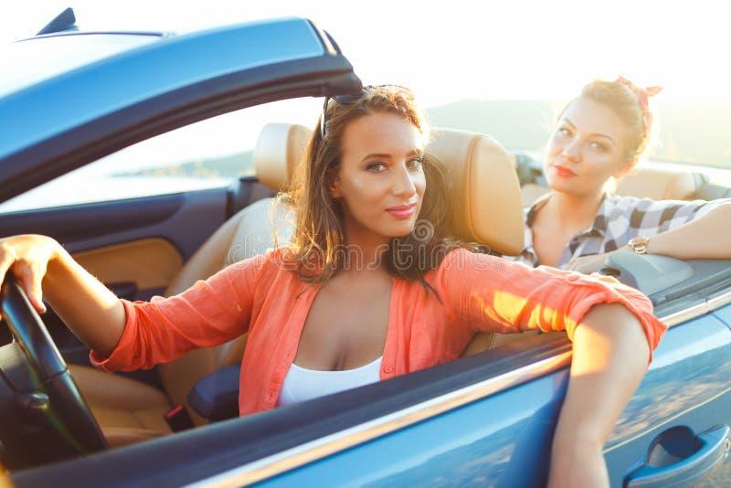 2 молодых счастливых девушки управляя cabriolet стоковые изображения rf