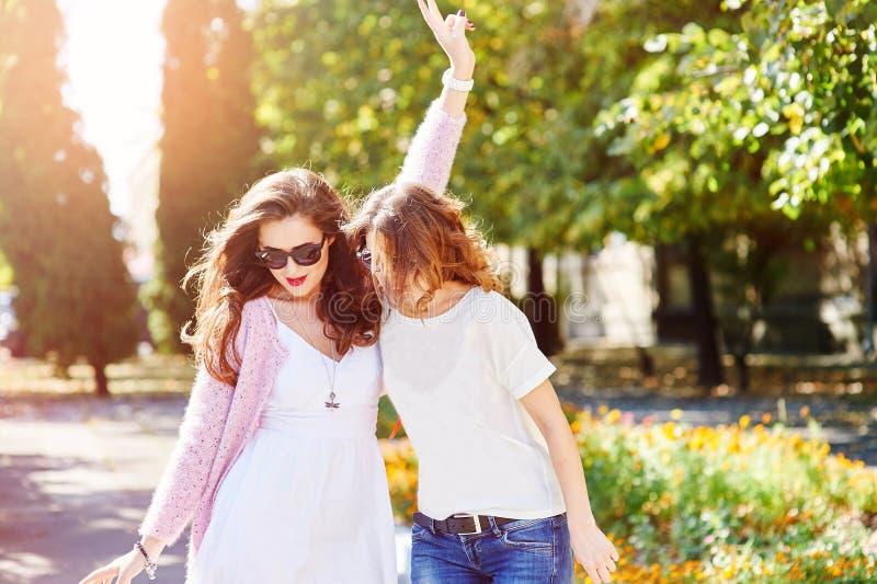 2 молодых счастливых женщины идя в город лета стоковые изображения rf
