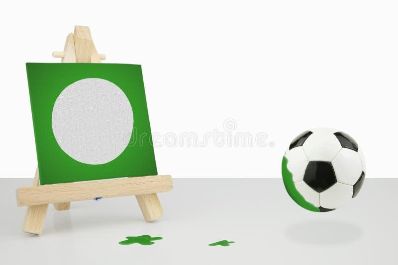 Мольберт художника с зеленой картиной футбола холста, футболом стоковые фотографии rf