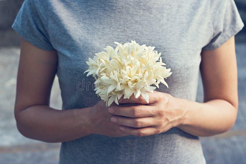 Моля женщина с белым букетом в руках для того чтобы показать уважение стоковые фотографии rf