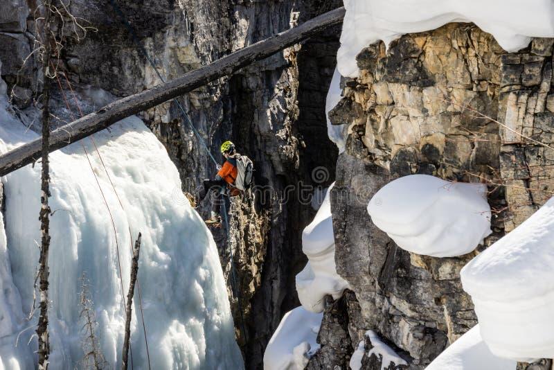 МРАМОРНЫЙ КАНЬОН, КАНАДА - 20-ОЕ МАРТА 2019: alpinists с рюкзаками подготавливая взбираться вниз льдом к каньону стоковое изображение rf