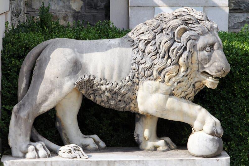Мраморный лев с шариком - старая скульптура в парке замка Peles, Sinaia, Румынии стоковые фото