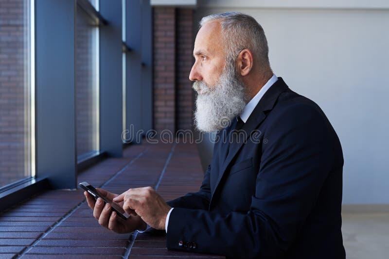 Мрачный мужчина смотря вне окно пока работающ в телефоне стоковое изображение rf