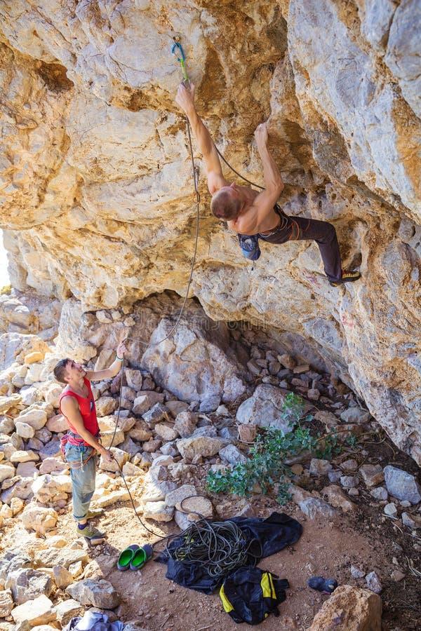 Мужская веревочка клиппирования альпиниста, его партнер belaying стоковое фото rf