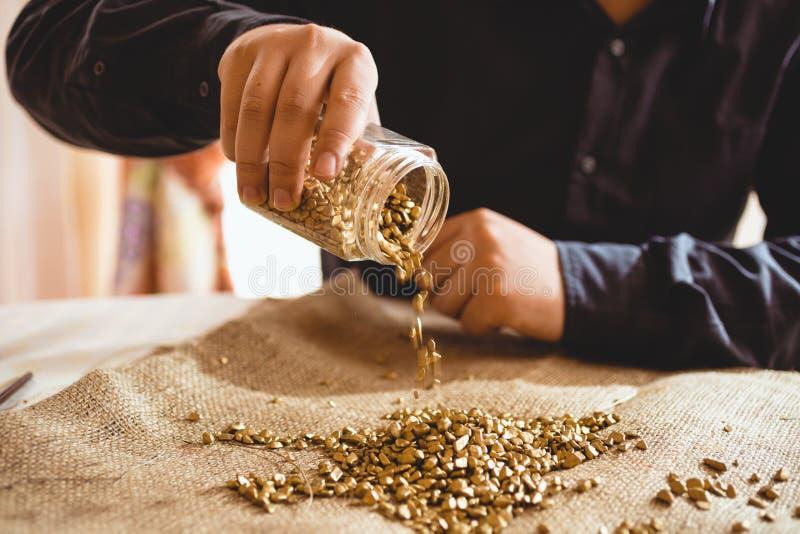 Мужская горнорабочая сидя на таблице и лить золоте из стеклянного опарника стоковые изображения