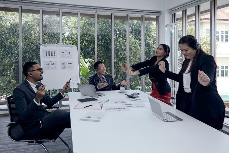 Мужская исполнительная власть и другая музыка штата слушая и танцевать в конференц-зале во время обсуждения отчете о продажи стоковая фотография