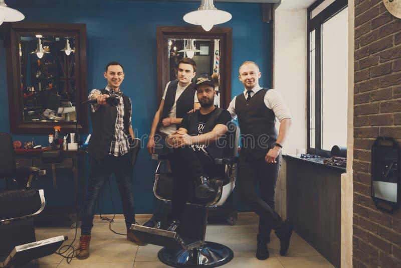 Мужская команда парикмахеров на современной парикмахерскае стоковое изображение rf