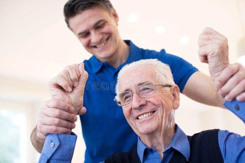 Мужская медсестра определяя старшую жертву хода путем поднимать оружия стоковые изображения rf