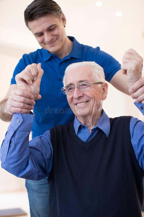 Мужская медсестра определяя старшую жертву хода путем поднимать оружия стоковая фотография rf