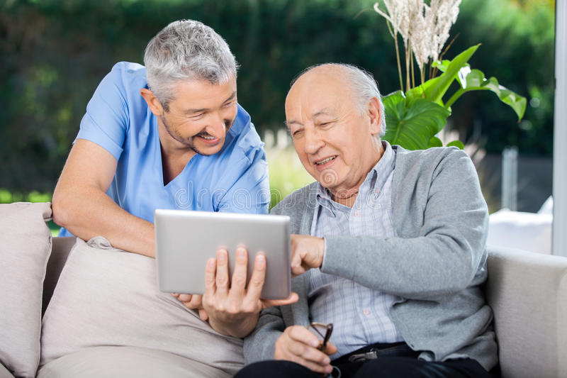 Мужская медсестра и старший человек усмехаясь пока использующ стоковая фотография rf