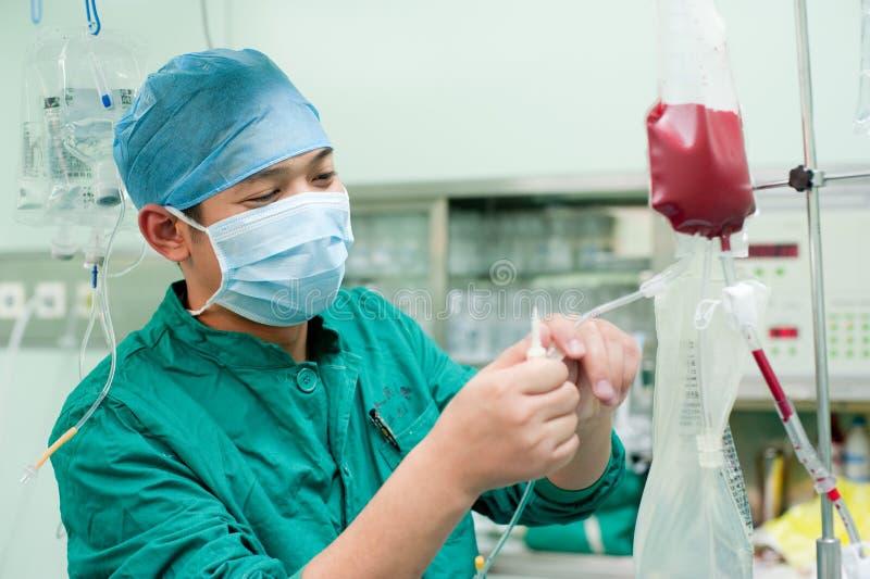 Мужская медсестра для того чтобы наблюдать сумкой крови стоковые изображения rf