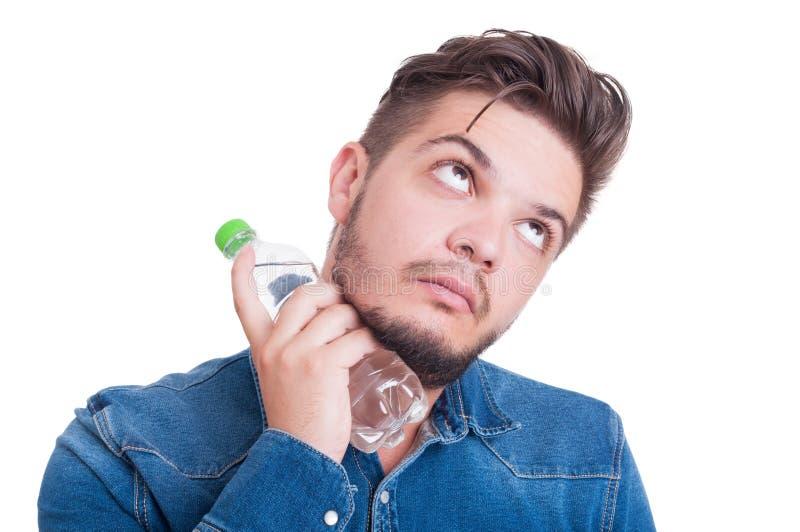 Мужская модель охлаждая его шею с холодной бутылкой с водой стоковая фотография