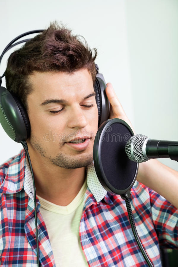 Мужская певица выполняя в студии звукозаписи стоковые изображения rf