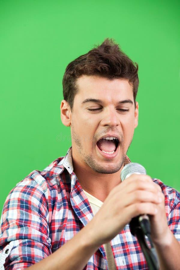 Мужская певица выполняя против зеленой стены стоковые изображения