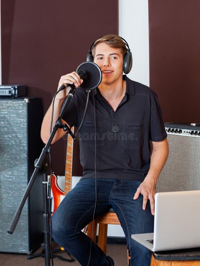 Мужская певица в вскользь выполнять на студии звукозаписи стоковое фото