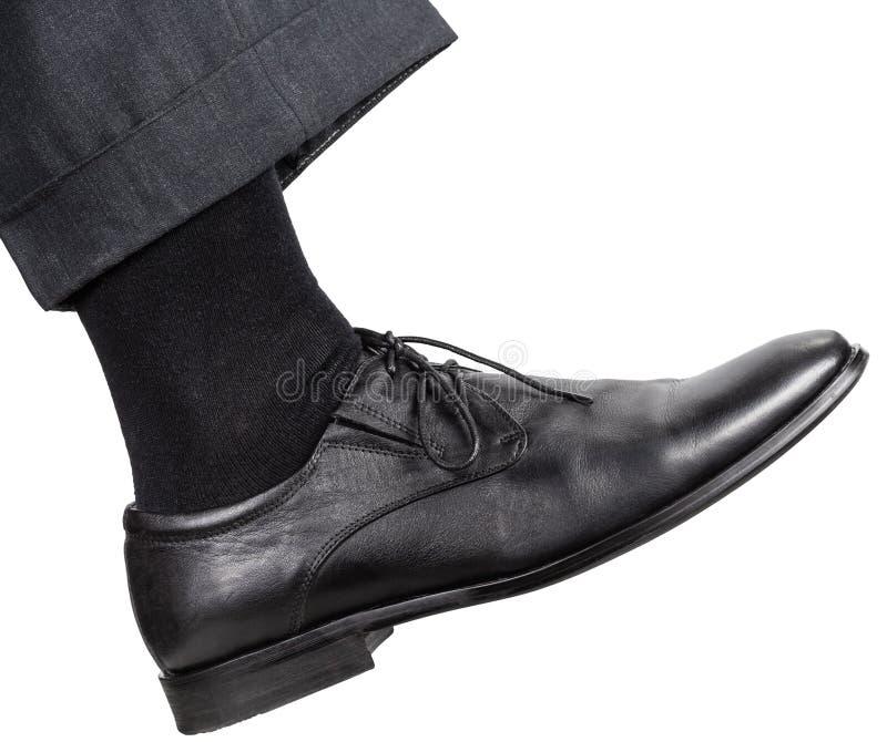 Мужская правая нога в черном ботинке предпринимает меры стоковое фото rf