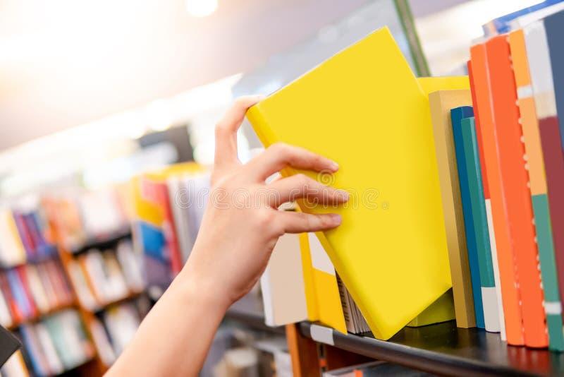 Мужская рука выбирая Желтую книгу от книжных полков стоковые фото