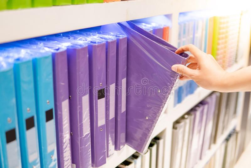 Мужская рука выбирая папку файла в магазине канцелярских принадлежностей стоковые фотографии rf