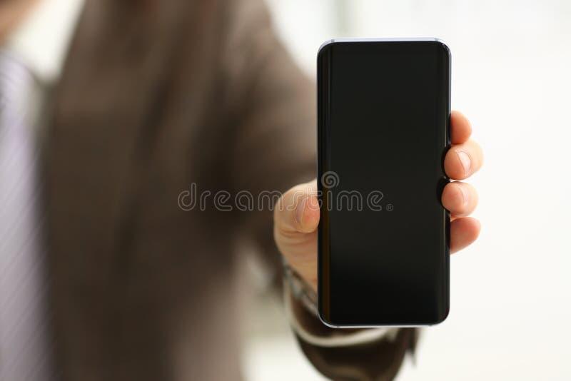 Мужская рука в шоу костюма в дисплее телефона камеры стоковые изображения