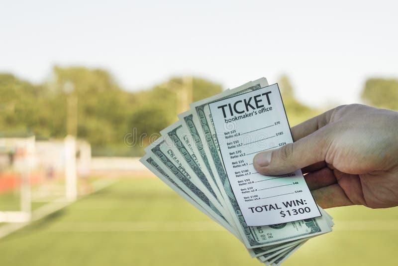 Мужская рука держа доллары денег и билет на фоне футбольного поля, конец-вверх букмейкера стоковые фотографии rf