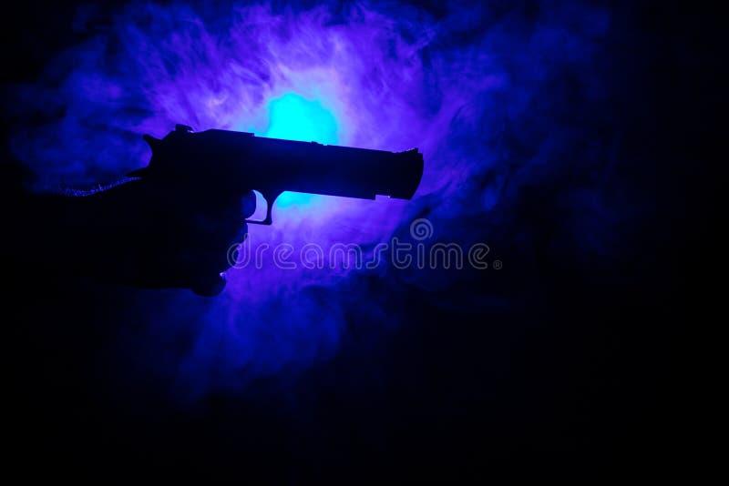 Мужская рука держа оружие на черной предпосылке с дымом (желтой белизной оранжевого красного цвета) покрасила задние света стоковое изображение rf