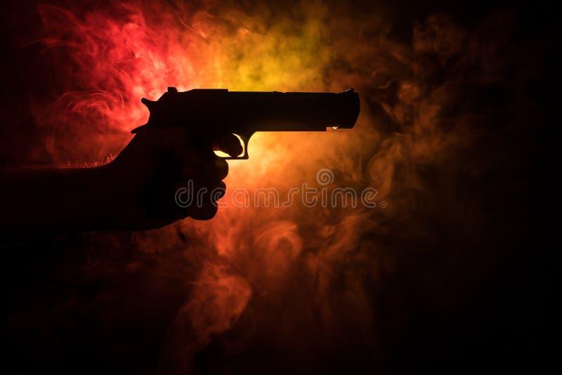 Мужская рука держа оружие на черной предпосылке с дымом (желтой белизной оранжевого красного цвета) покрасила задние света стоковая фотография rf