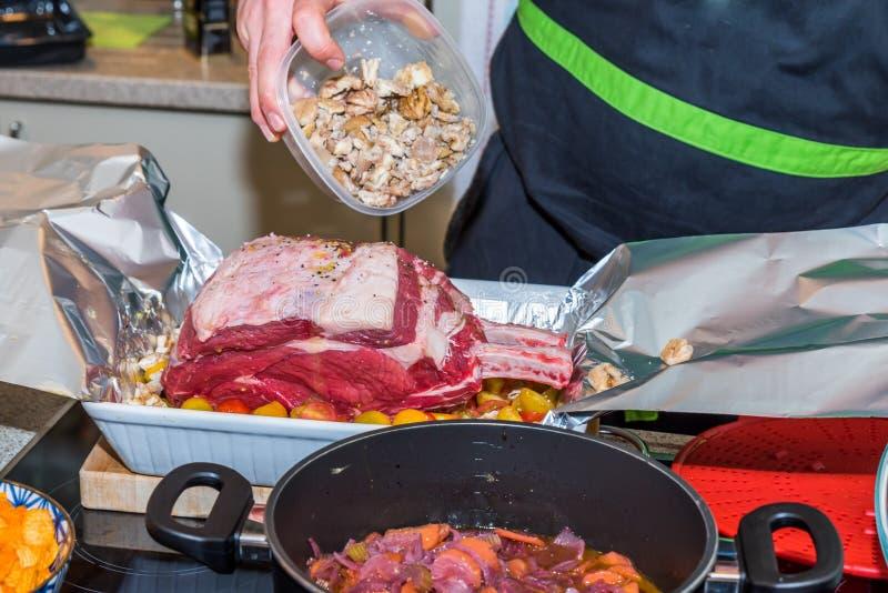 Мужская рука держа пластмасовый контейнер и распыляя сваренные каштаны над сырцовым стейком нервюры говядины для жарить в духовке стоковая фотография