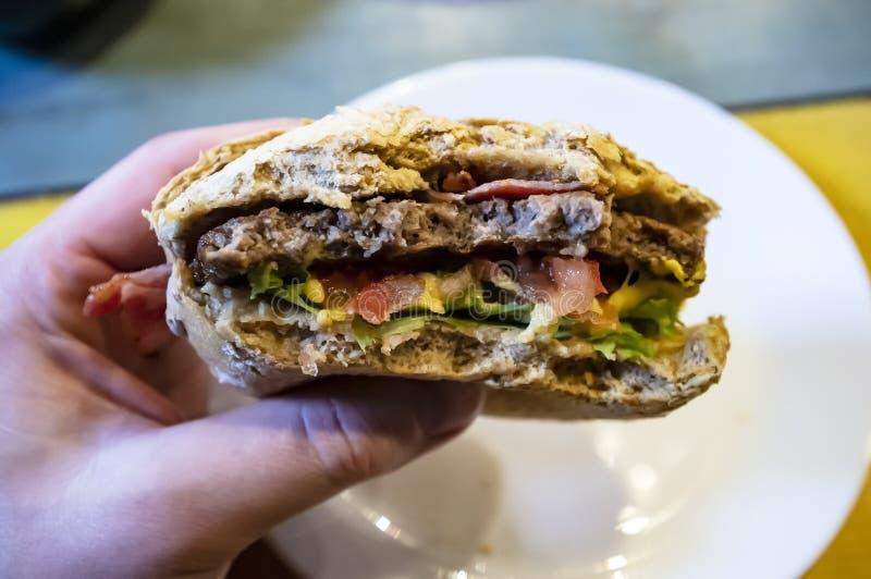 Мужская рука держа сдержанный, очень вкусный cheeseburger, на фоне плиты стоковая фотография rf