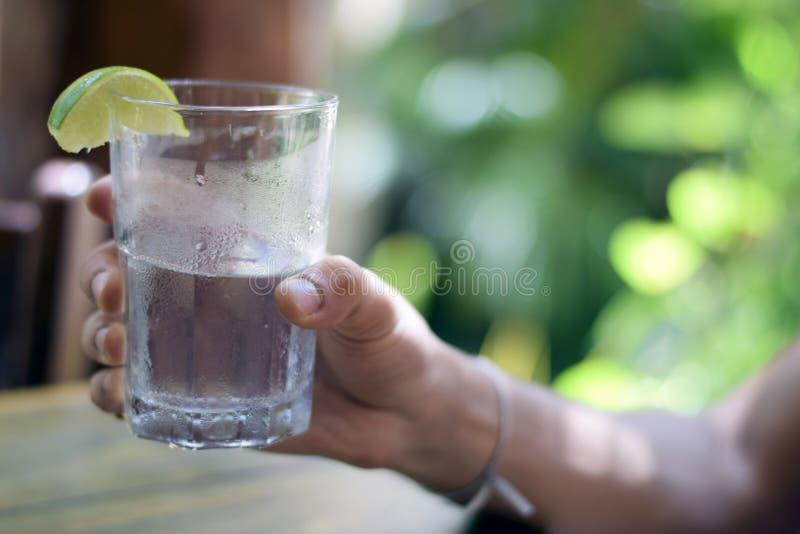 Мужская рука держа стекло воды стоковые изображения