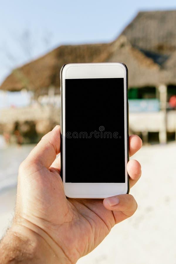 Мужская рука держа smartphone с пустым экраном стоковое фото
