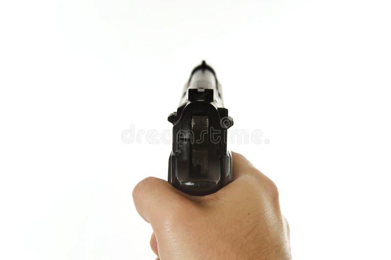 Мужская рука держа оружие включения направляя в субъективную точку зрения POV изолированную на белой предпосылке стоковые изображения