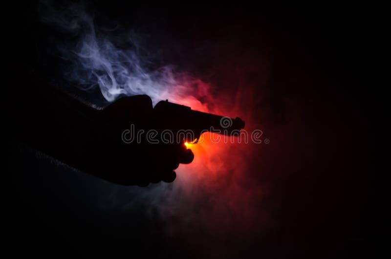 Мужская рука держа оружие на черной предпосылке с дымом (желтой белизной оранжевого красного цвета) покрасила задние света, конце стоковые фото