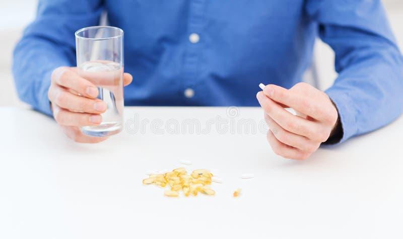 Мужская рука держа пилюльку и стекло воды стоковое фото