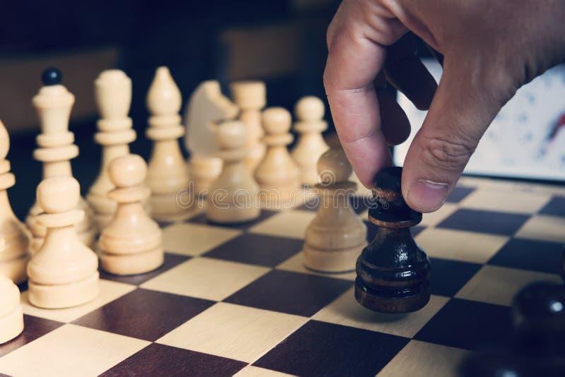 мужская рука играя шахмат на свете запачкала предпосылку черная пешка в руке начала игры в шахматы стоковые изображения rf
