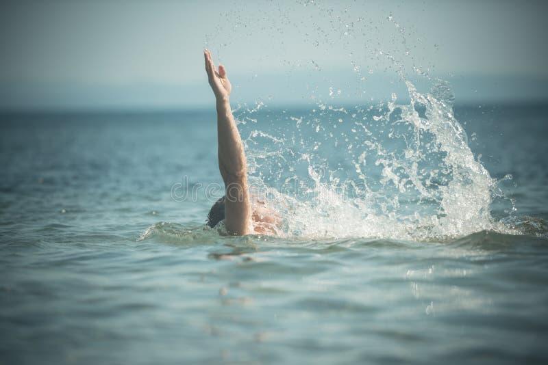 Мужская рука из моря с брызгает воды Плавая концепция Гай плавая под морской водой, горизонтом на предпосылке, задней стоковое изображение rf