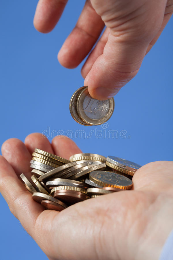 Мужская рука кладет монетки в ладонь его партнер стоковое фото