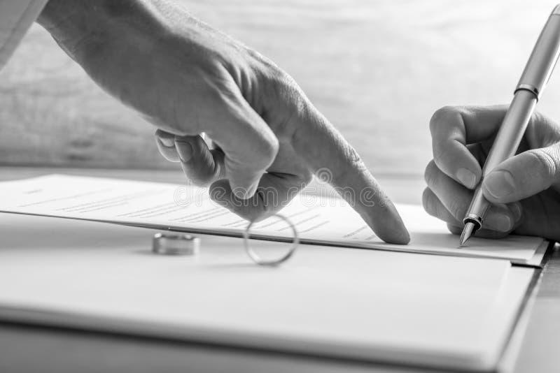Мужская рука указывая к женщине где подписать законные бумаги развода стоковые изображения