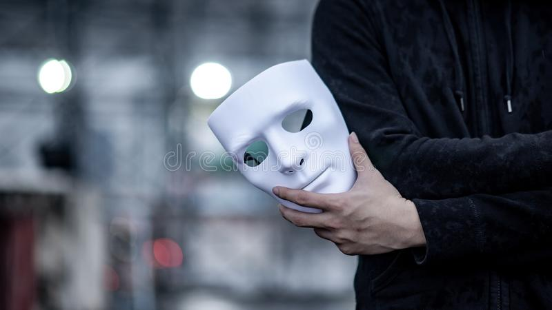 Мужская рука черного человека куртки держа белую маску Анонимный социальный маскировать или главная концепция упадочного разлада стоковое фото