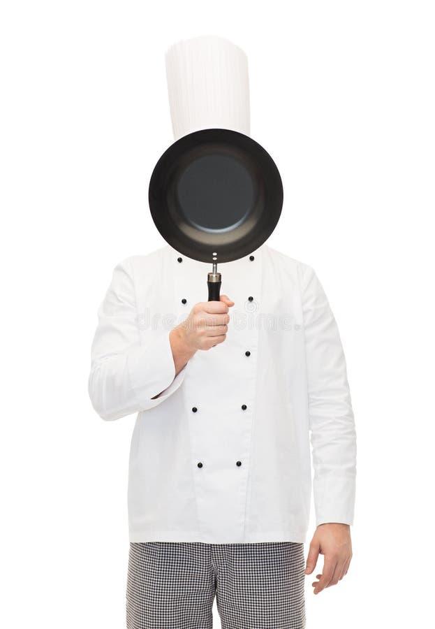 Мужская сторона заволакивания кашевара шеф-повара с сковородой стоковые фото