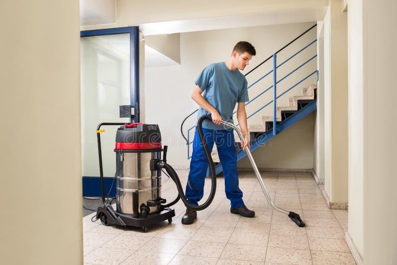 Мужская чистка работника с пылесосом стоковое изображение