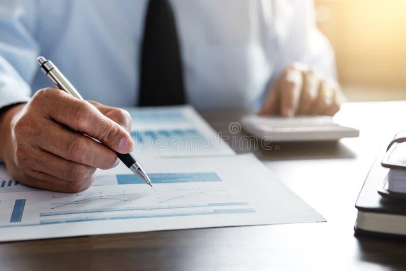 Мужские вычисления бухгалтера и анализировать финансовые данные по диаграммы стоковое фото