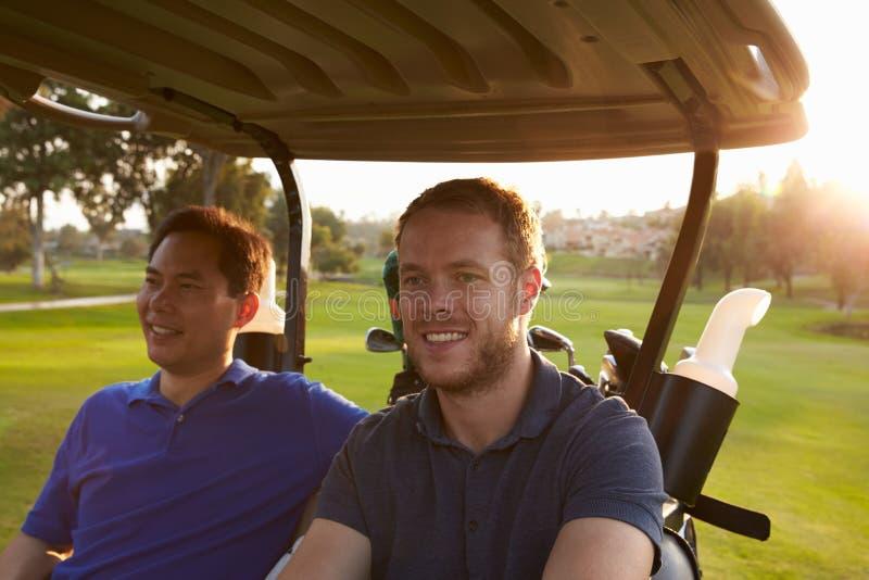 Мужские игроки в гольф управляя багги вдоль прохода поля для гольфа стоковые изображения