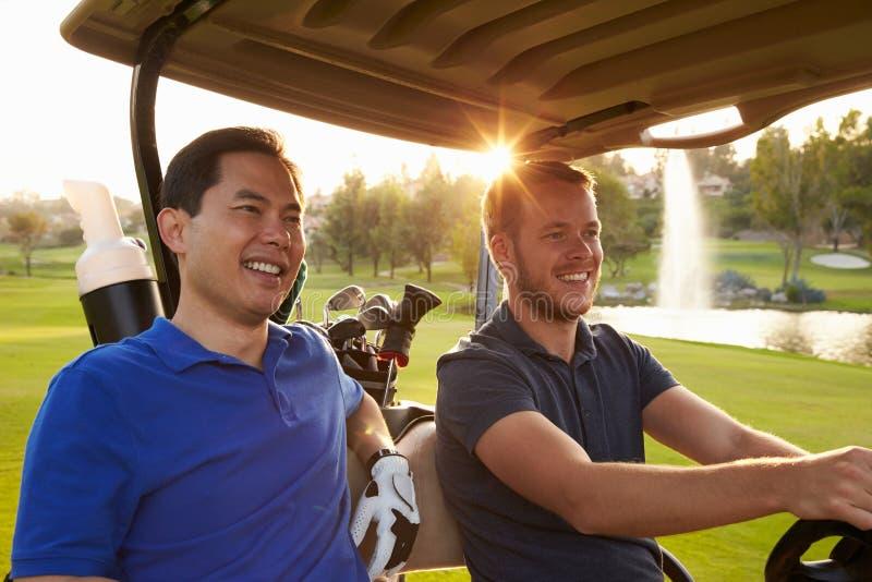 Мужские игроки в гольф управляя багги вдоль прохода поля для гольфа стоковая фотография