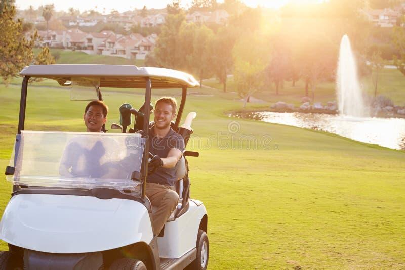 Мужские игроки в гольф управляя багги вдоль прохода поля для гольфа стоковая фотография rf