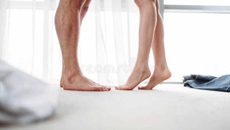 Мужские и женские ноги, интимные игры в спальне стоковая фотография