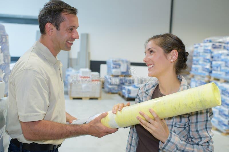 Мужские и женские работники анализируя бумаги в фабрике стоковая фотография