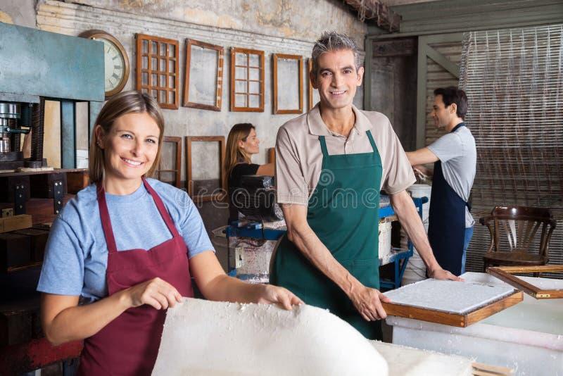 Мужские и женские работники делая бумаги в фабрике стоковая фотография rf