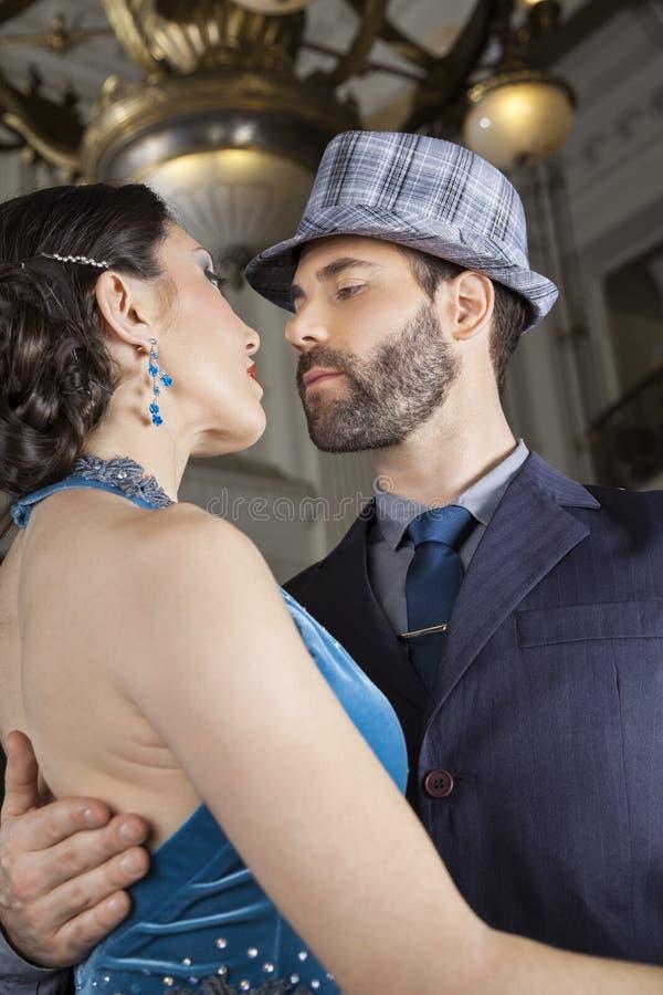 Мужские и женские танцоры выполняя танго в кафе стоковое фото