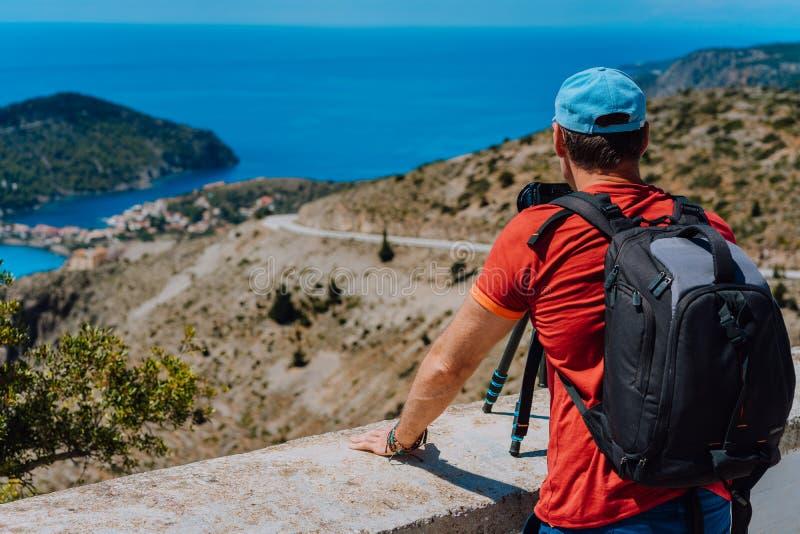 Мужские каникулы летнего отпуска на Kefalonia Греции Фотограф с рюкзаком наслаждаясь захватом среднеземноморской деревни стоковое фото rf